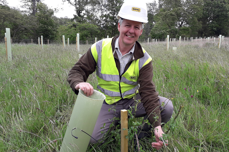 Landscape architect Mark Simmons with one of the first 3,500 saplings that were planted on the Bradley surface mine site last year, (2019), a number which will rise to around 10,500 by the end of the project