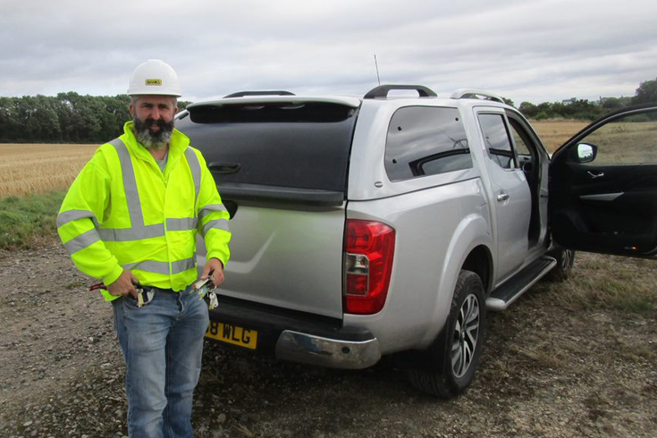 Pictured above: Tommi McElroy standing at the rear of his Nissan Navara on site at Penny Hill Wind Farm