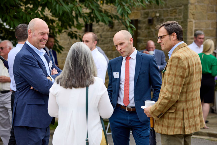 <p>Pictured above: Gary Morgan (left) and Rob Ormrod of Banks (navy suit and red tie) talk to guests at the event</p>